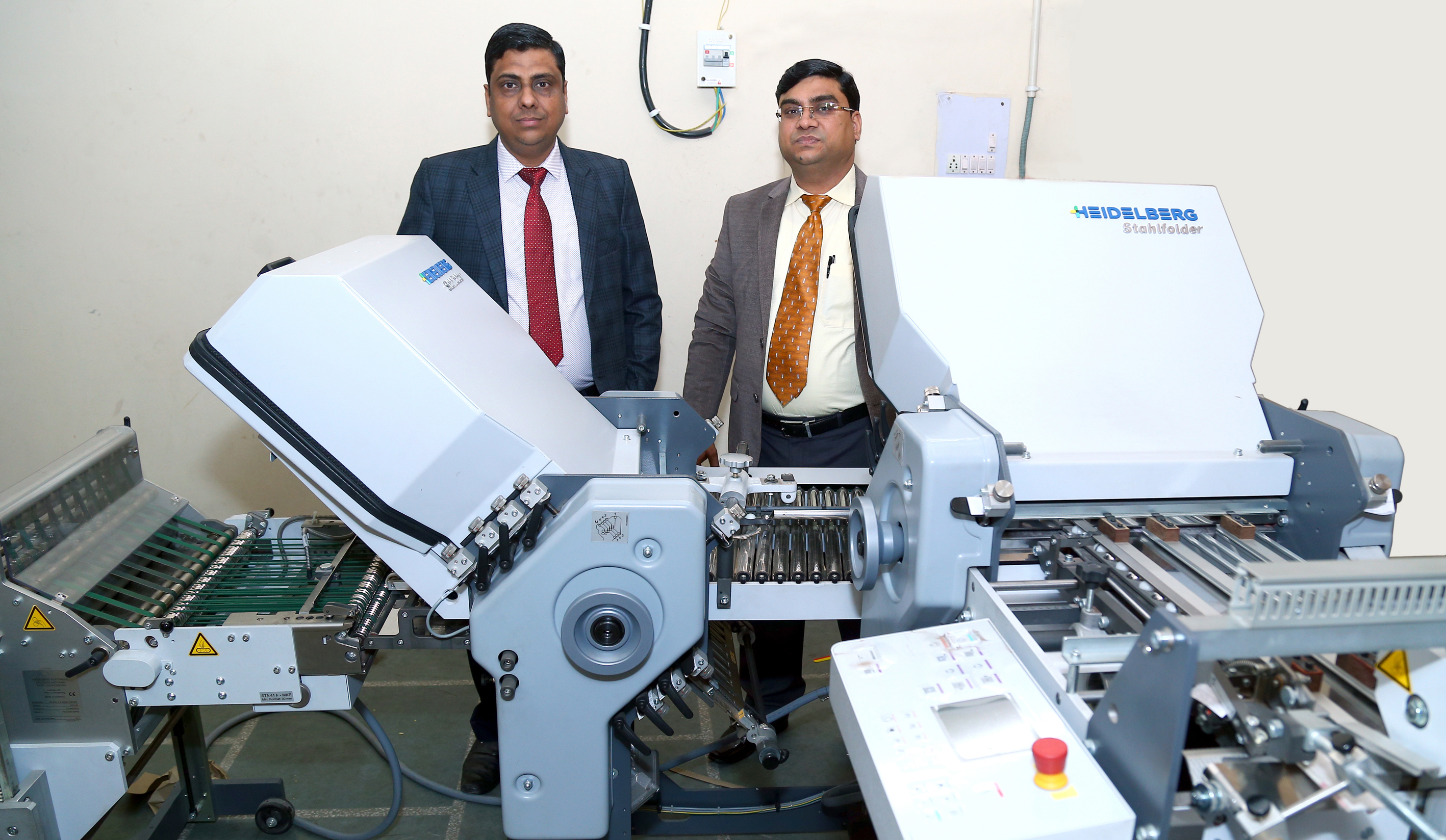 (l-r) Pradeep Kumar Jain and Anuj Kumar Jain with the Stahl paper folding machine